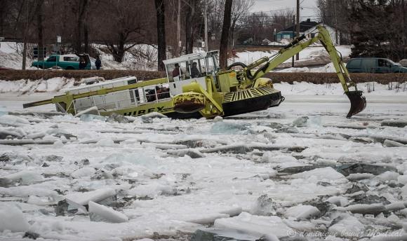 Pour éviter un embâcle (accumulation de blocs de glace qui fait barrage, on utilise une pelle amphibie pour casser la glace.