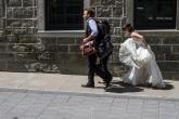 Dans la ruelle, pas loin, la bientôt jeune mariée court la traine la main.,