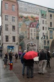 """Devant la fresque dite """"des Québécois, sur la place royale."""